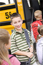 Smiling boy in front of school bus