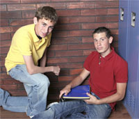 Two boys sitting by lockers