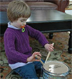 Little girl in purple sweater with drum