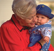 Grandmother holds baby in blue hat