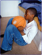 Boy with basketball alone in room