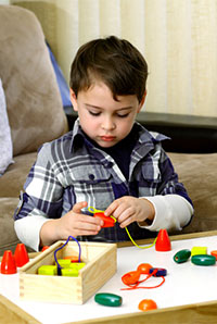 photo of boy doing applied behavior analysis therapy at a table with blocks, istock