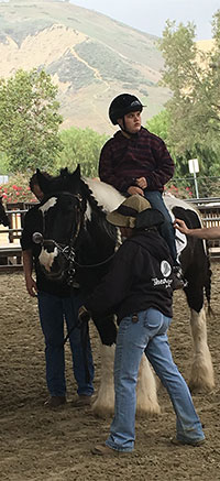 Photo of Adam Lloyd participating in therapeutic horseback riding lesson, illustrating article on a study finding benefits in autism