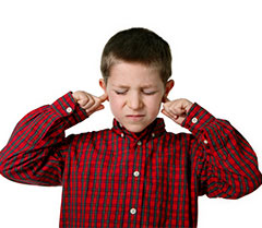 Photo of boy covering ears, illustrating noise sensitivity in autism