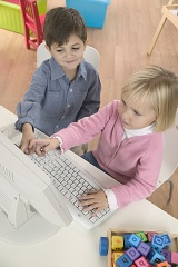 Photo of preschool boy and girl at computer
