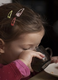 Photo of toddler girl drinking from cup, autism in girls article