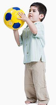 Photo of boy holding soccer ball to illustrate article about physical fitness and autism