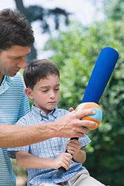photo of man coaching basebal to a boy, illustrating article about physical fitness and autism