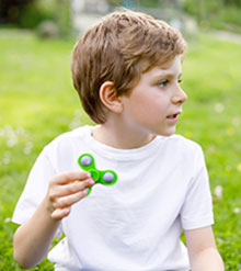 photo of boy holding a spinning toy