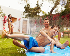 photo of family enjoying water slide in back yard