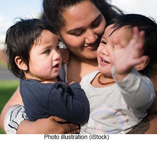 photo illustration of mother holding twins from iStock