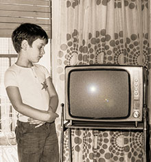 photo illustration of boy looking at 1970s era television
