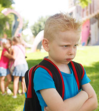 photo of boy feeling isolated on playground, illustrating article on autism stigma and social rejection