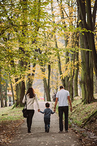 Parents and child walking the path, illustrating article about getting an autism diagnosis and early intervention
